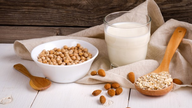 Vegan non dairy milk in glass and milk alternatives ingredients like a nut, almond, soy, oat on wooden table with kitchen towel. Organic food and drink, health care, diet and nutrition concept. Soy, oat, almond, coconut milk. iStock