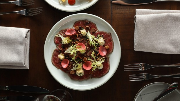 Beef carpaccio with anchovy mayonnaise, shiso dressing, smoked crouton, crispy garlic, puffed wild rice and frisee.