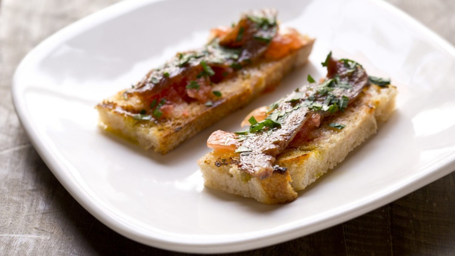 Anchovy with tomato and garlic on grilled bread.