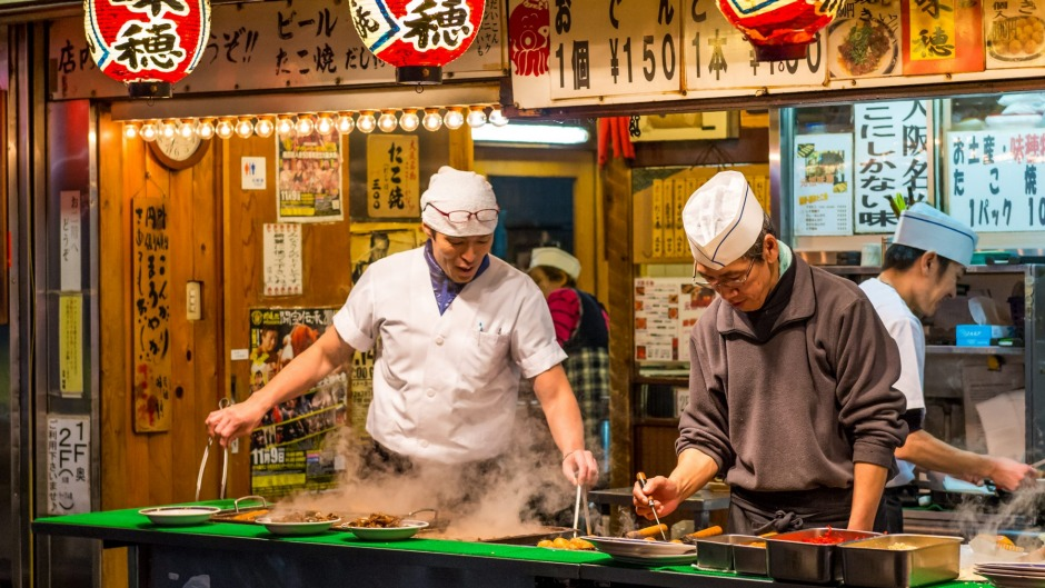 Street food vendors cooking takoyaki in Osaka, Japan.