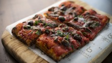 Puttanesca pizza a taglio is all crisp crust and salty, savoury topping of tomato sugo, anchovy, olives and basil.