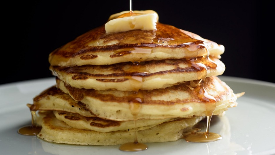 A stack of perfect buttermilk pancakes with butter and maple syrup.