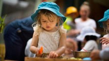 Two-year-old Maggie preparing food at Clarendon Children's Centre.