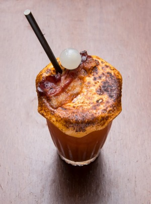 Bloody Mary topped with melted cheese, bacon and pickled onion.