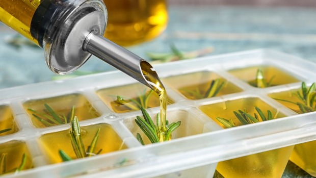 Pouring olive oil into ice cube tray with rosemary on table, closeup. freezing herbs. Frozen food. Freezer stocked with containers of frozen fruit and vegetables. Generic image downloaded for Good Food freezing food story March 2020.