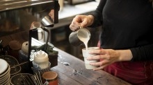 Barista Claire serves up a coffee in a keep cup at Something for Jess cafe in Chippendale.