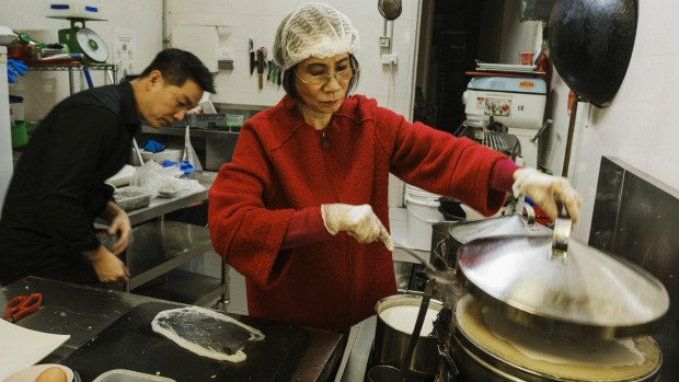 Anthony Dinh with his mother Kim Thanh making steamed rice paper rolls.