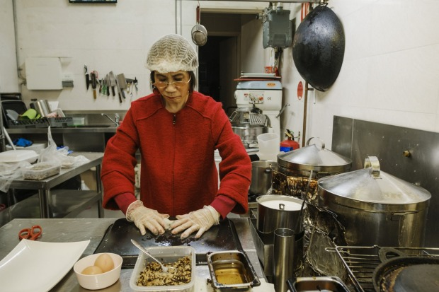 Kim Thanh cooking in her son Anthony Dinh's Vietnamese restaurant.