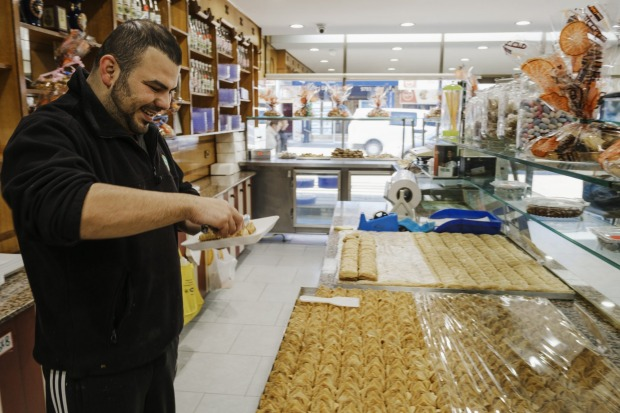 Mohammad El Basha samples a dessert in between customers at the Chehade El Bahsa & Sons Sweets shop.
