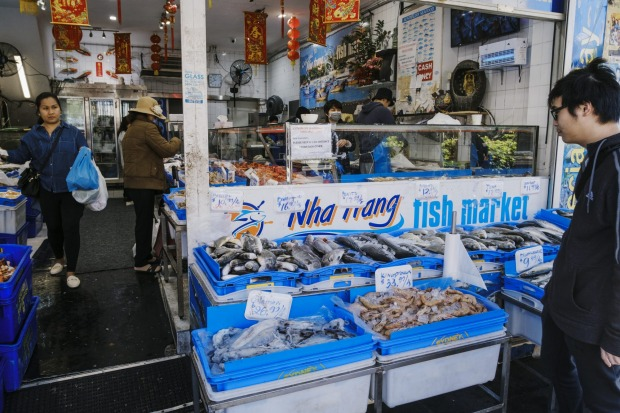 Customers check out the fresh seafood available at the Wha Wang Fish Market.
