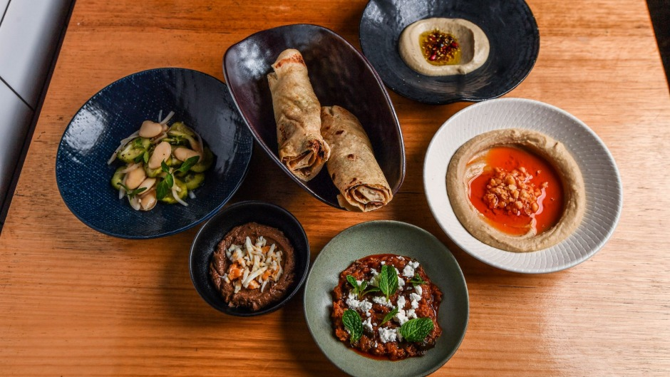 Clockwise from left: House-made hummus, spicy mizrahi zucchini, chopped liver, Lebanese cucumber and lima beans and baba ...