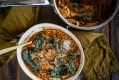 Smoky tomato soup with shredded chicken, cavolo nero and cheese.