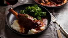 Lamb shanks cooked in red wine sauce and served with mashed potato and kale.