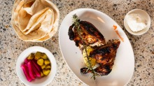 Charcoal chicken half with Lebanese bread, toum and pickles.