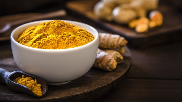 Front view of a turmeric powder bowl on a rustic wooden table. Alongside the bowl is a wooden serving scoop filled with turmeric powder and are at the left lower corner. At the right top corner is a defocussed wooden cutting boar with quinoa seeds on top. Low key DSLR photo taken with Canon EOS 6D Mark II and Canon EF 24-105 mm f/4L Turmeric iStock