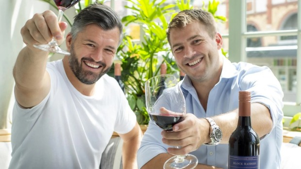 Former Wallabies Adam Ashley Cooper (left) and Drew Mitchell with their Backline Wines shiraz.