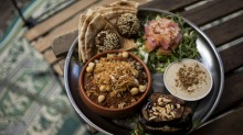 The mixed platter comes with fried eggplant, pickles, tahini dip and a stack of flatbread.