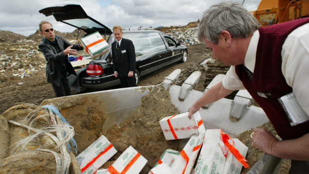 Will Studd burries raw milk cheese from a hearse while a quarantine officer checks everything is in order in the early 2000s.
