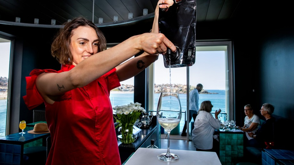 Sommelier Lillia McCabe pouring a glass of wine from bag to glass.