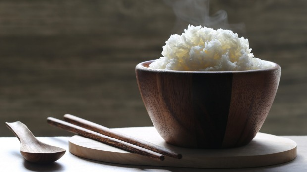cooked rice in wood bowl with smoke rising on dark background Rice generic iStock
