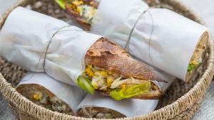 Chicken and corn baguettes, wrapped and packed for a picnic.