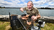BBQAroma owner Nick Angelucci cooking on his portable Ferraboli picnic grill in Leichhardt Park.