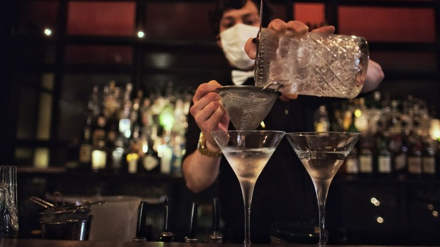 Observing guidelines, a masked bartender mixes a drink at The Supper Club in Melbourne.