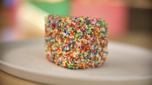 The fairy bread popcorn lamington is dunked in hundreds and thousands.
