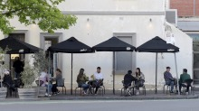Customers sit at socially distanced tables outside a Carlton restaurant.
