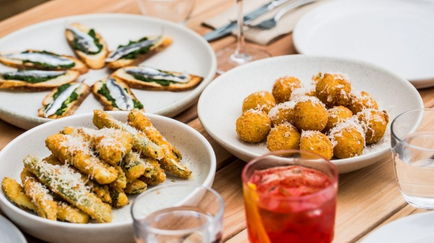 Expect an Italian restaurant menu, including white anchovy crostini (left rear), zucchini fritti (front) and arancini.