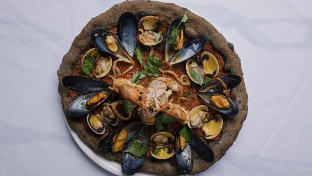 The grey, squid ink-infused base of a pizza Amalfitana is scattered with lightly cooked seafood.