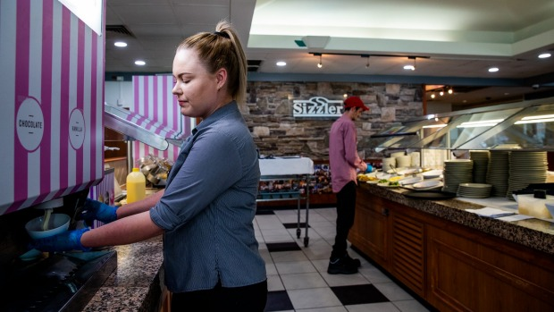 A staff member at Sizzler Campbelltown pulls soft serve for a table of customers.