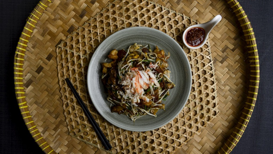 The char kwai teow with crab meat also includes wads of salty, oil-slicked noodles tossed with prawns, chives, crunchy ...