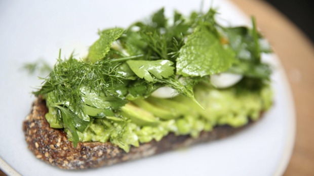 Avocado on toast with softly-set egg, crushed peas and herbs.