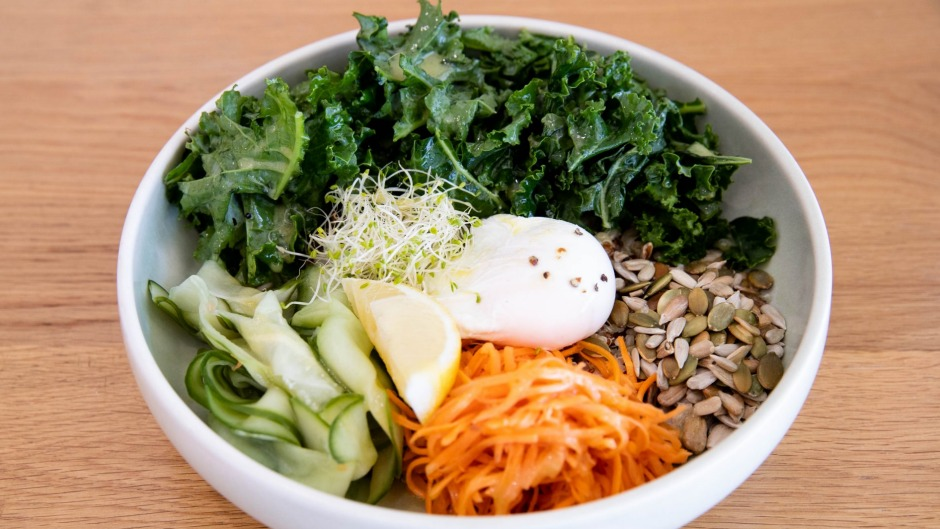 The breakfast bowl is served with poached egg, brown rice, raw kale and quinoa.