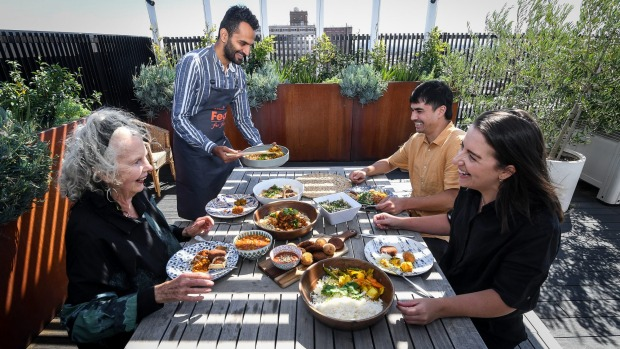 Lakshay Gumber (standing) serves a Middle Eastern feast to friends an neighbours on the rooftop of his Brunswick ...
