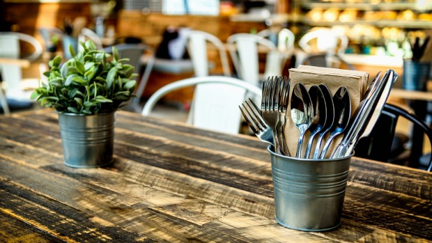 A warm cafe interior with wooden table, cutlery, pot plant and food counter in the background Generic cafe restaurant iStock