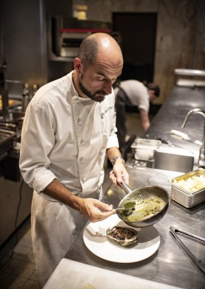 Rockpool Bar & Grill executive chef Corey Costelloe finishes a local abalone with butter.