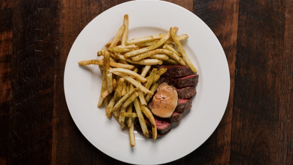The bavette steak comes pink and glistening inside, and darkly crusty outside, smothered in skinny, skin-on fries.
