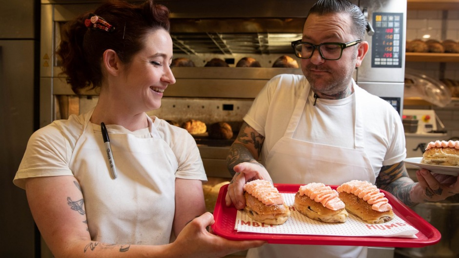 Ben Milgate and Alyce Bennett at Humble Bakery with a batch of fresh finger buns.