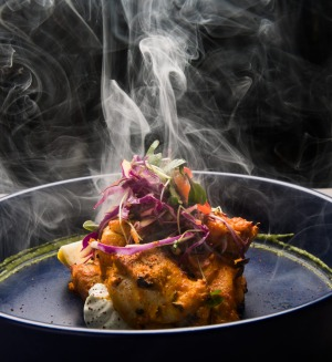 Chicken tikka is presented with a puff of smoke.