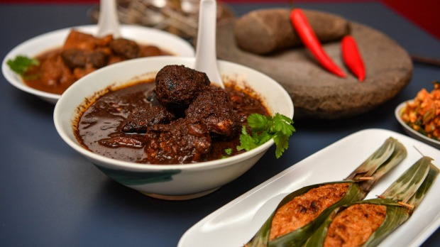 Babi pongteh (braised pork in fermented soy beans, left) and ayam keluak (chicken braised with keluak nuts, centre) are ...