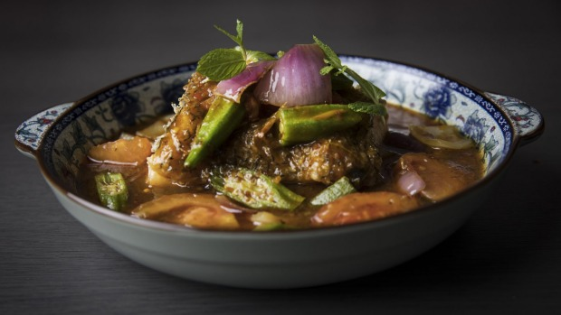 Assam nonya curry with toothfish, a sweet-and-sour dish studded with okra, tomato and red onion.