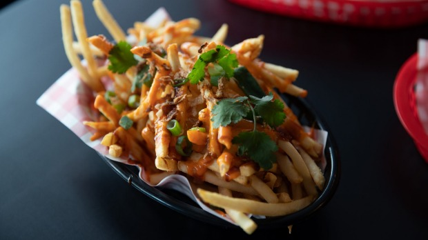 A bowl of pho-fries: hot chips topped with Sriracha mayo, hoisin, fried shallots and coriander.