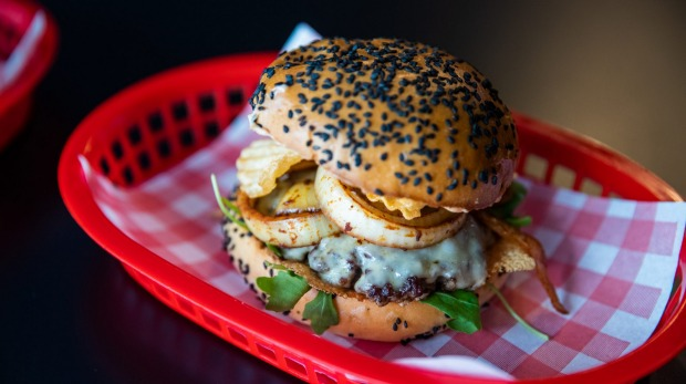 The Wild West burger with a sesame-flecked bun, juicy beef patties, Havarti cheese, grilled onions and crinkle chips.